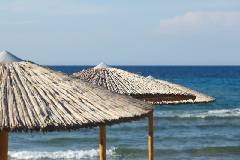 Strohregenschirme auf Seehintergrund lizenzfreie stockfotografie