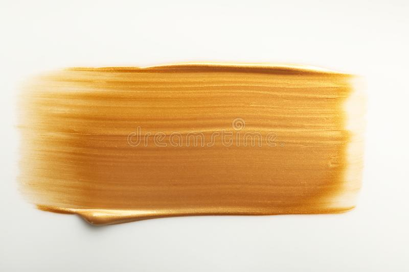 Stroke of gold paint isolated on white. Top view stock photography
