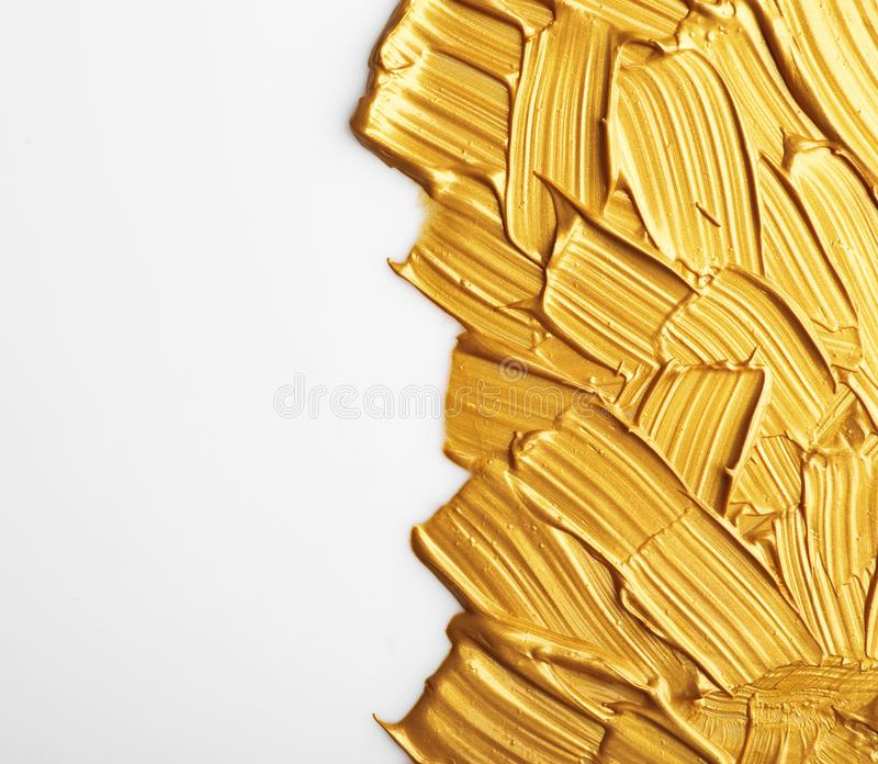 Strokes of gold paint  on white. Top view stock photos