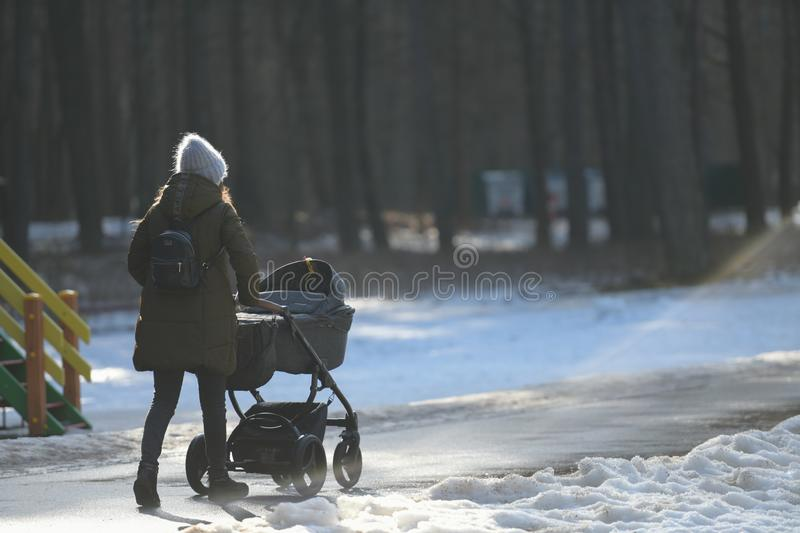 Stroller walk in the winter park. Mother walks with a stroller on a snowy winter day. A young mother walks with a stroller on a. Snowy winter day royalty free stock photography