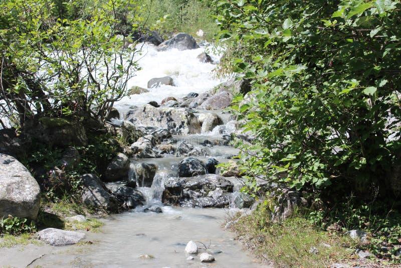 Strom des Wassers fließend in einen Fluss stockbild