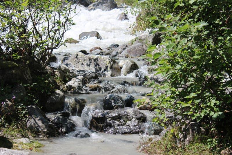 Strom des Wassers fließend in einen Fluss stockfotos