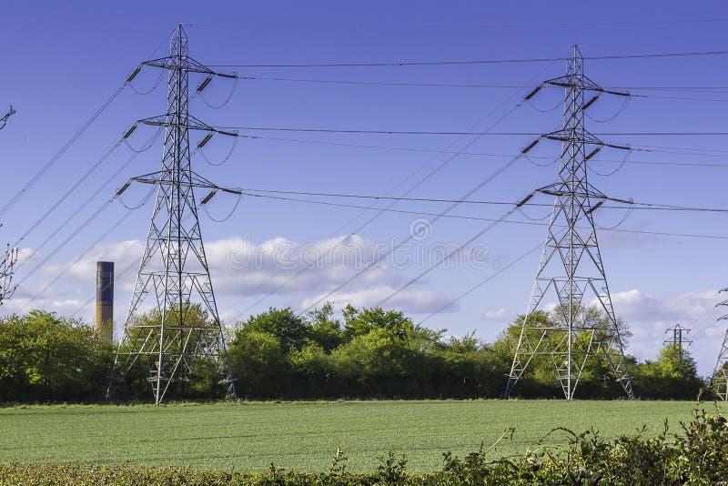 Strom-Masten auf dem Gebiet stockbild
