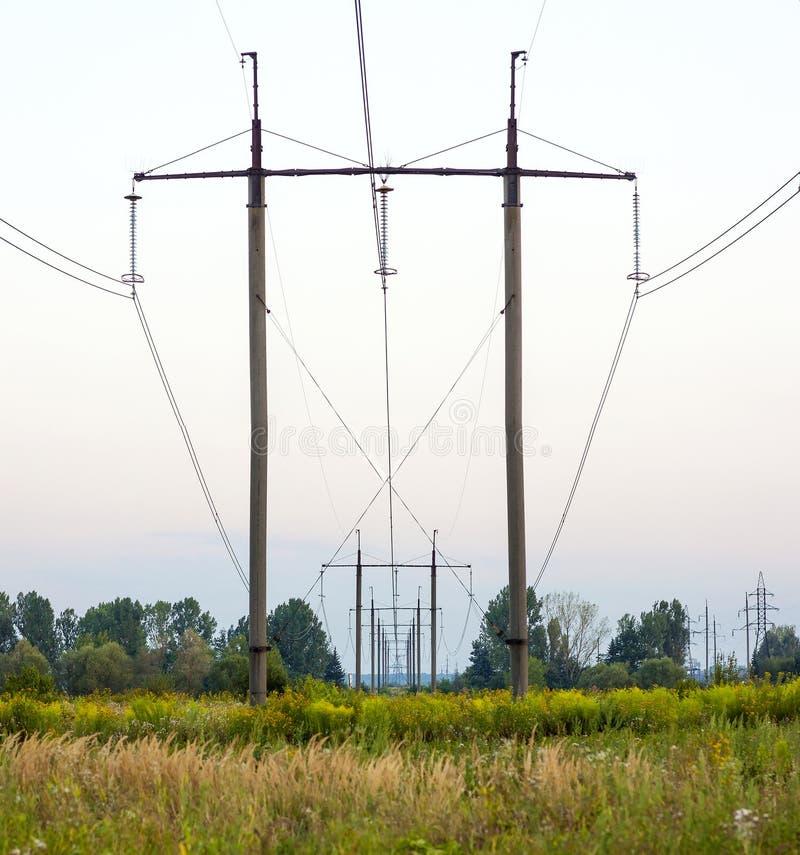 Strom-Masten, die weg auf dem Gebiet schleppen Macht-Getriebe PO lizenzfreies stockbild
