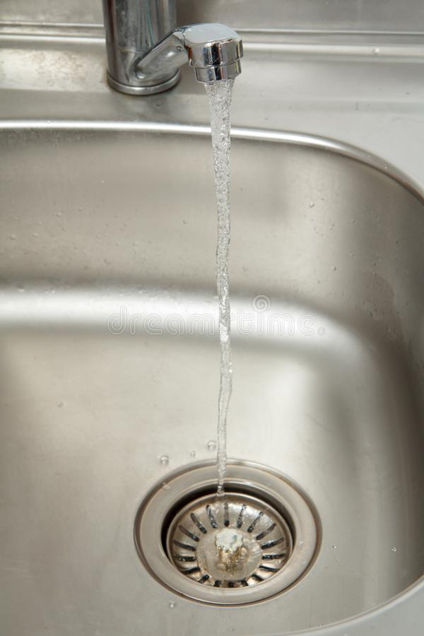 Strom von Wasserströmen von einem offenen Chromhahn lizenzfreies stockfoto