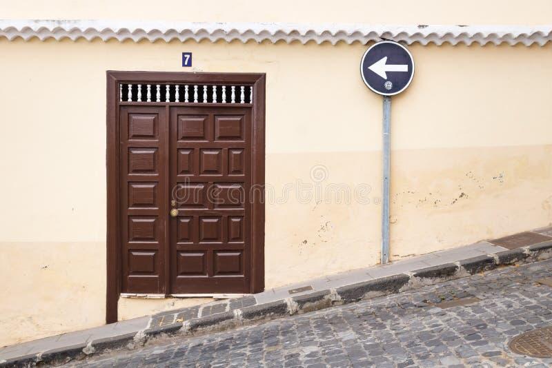 Stroma ulica z drewnianym wejściowym drzwi i lewym znakiem ulicznym, La Orotava, Tenerife, wyspy kanaryjska, Hiszpania zdjęcie stock