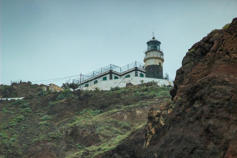 Strome wysokie lawy skały falezy dalej na wschodzie Tenerife Denna latarnia morska, naturalny nieba tło zdjęcia stock