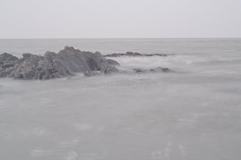 Stromende oceaan over rotsen stock afbeelding