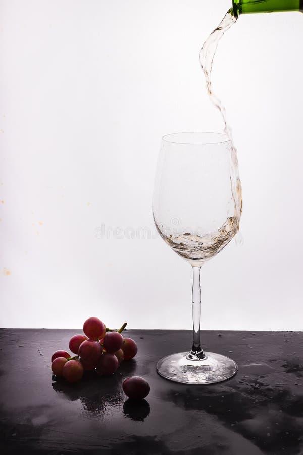Stromende wijn op witte achtergrond en druif stock fotografie