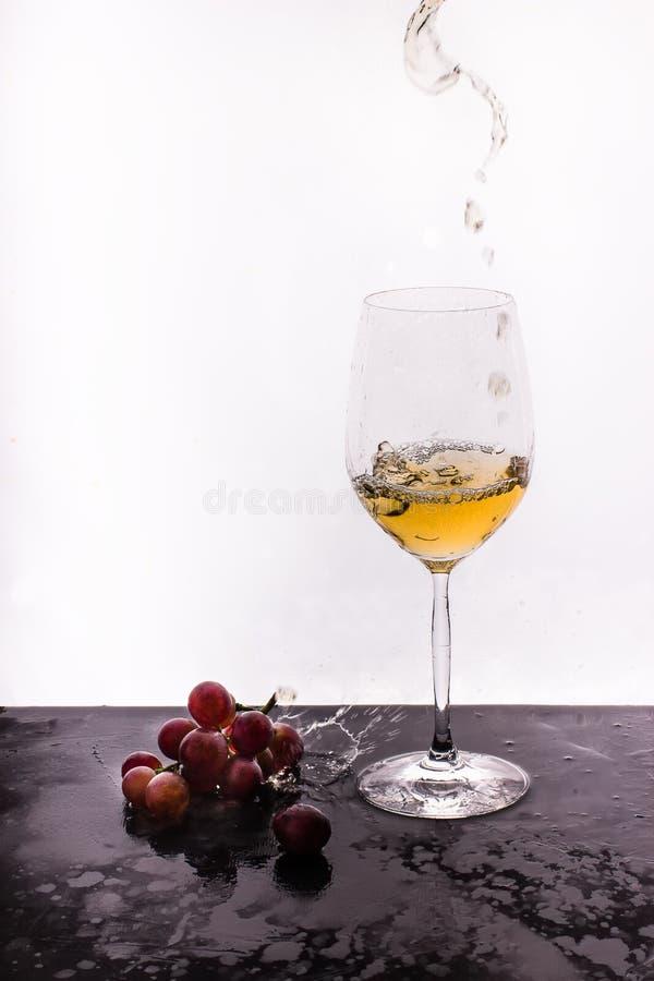 Stromende wijn op witte achtergrond en druif stock afbeeldingen
