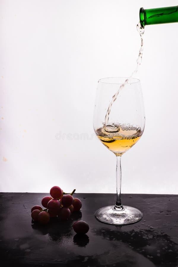 Stromende wijn op witte achtergrond en druif royalty-vrije stock fotografie