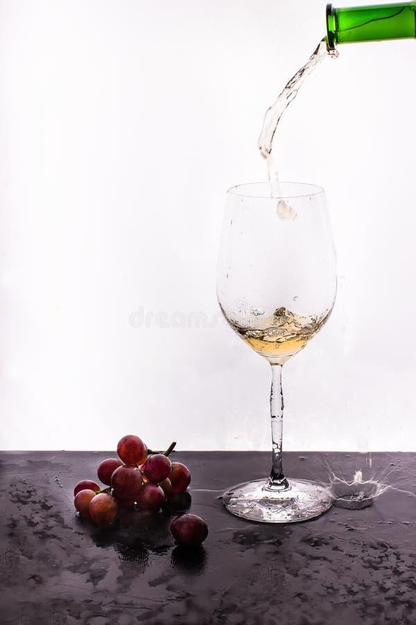 Stromende wijn op witte achtergrond en druif royalty-vrije stock foto