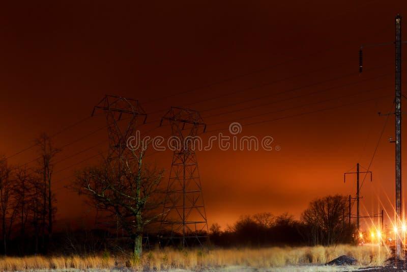 Stromkabel-Fernsehtürme auf dem Sonnenuntergangausdehnen lizenzfreies stockfoto