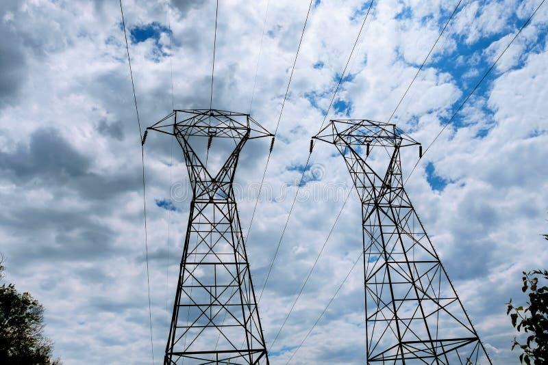 StromKraftwerk bei einem Sonnenuntergang Unterstützung von elektrischen Leitungen Wolken im Himmel - stufen Sie Betriebsgefahr ei lizenzfreies stockbild