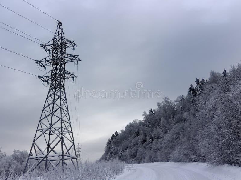 Stromleitung entlang Schneegebirgsstraße lizenzfreie stockfotos
