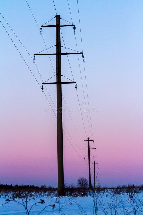 Stromleitungen auf schneebedecktem Feld des Winters bei Sonnenuntergang Elektrischer HochspannungsFreileitungsmast Apfelbaum, Son lizenzfreies stockbild
