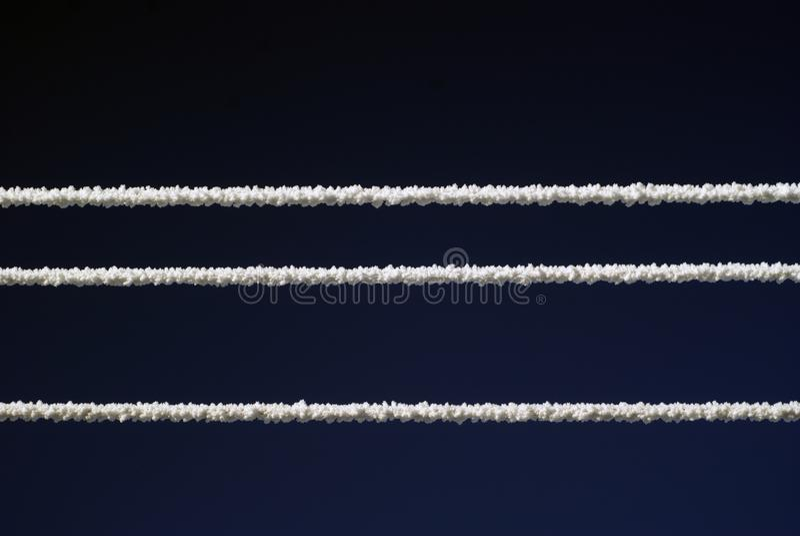 Stromleitungen umfasst mit Schnee im Frostwetter auf Hintergrund des bewölkten Himmels stockbilder