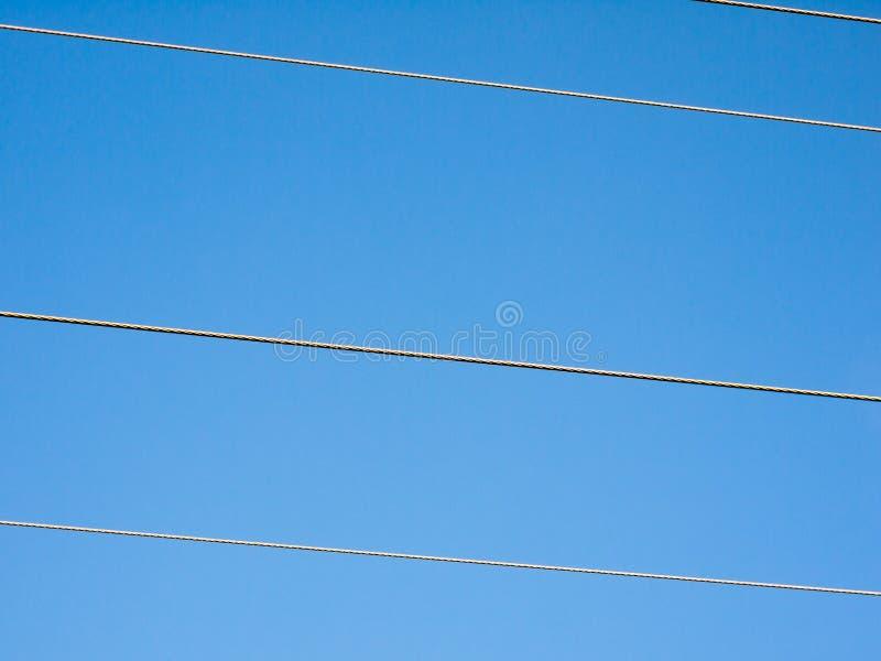 Strommast verdrahtet Ausschnitt über Hintergrund des blauen Himmels stockfotografie