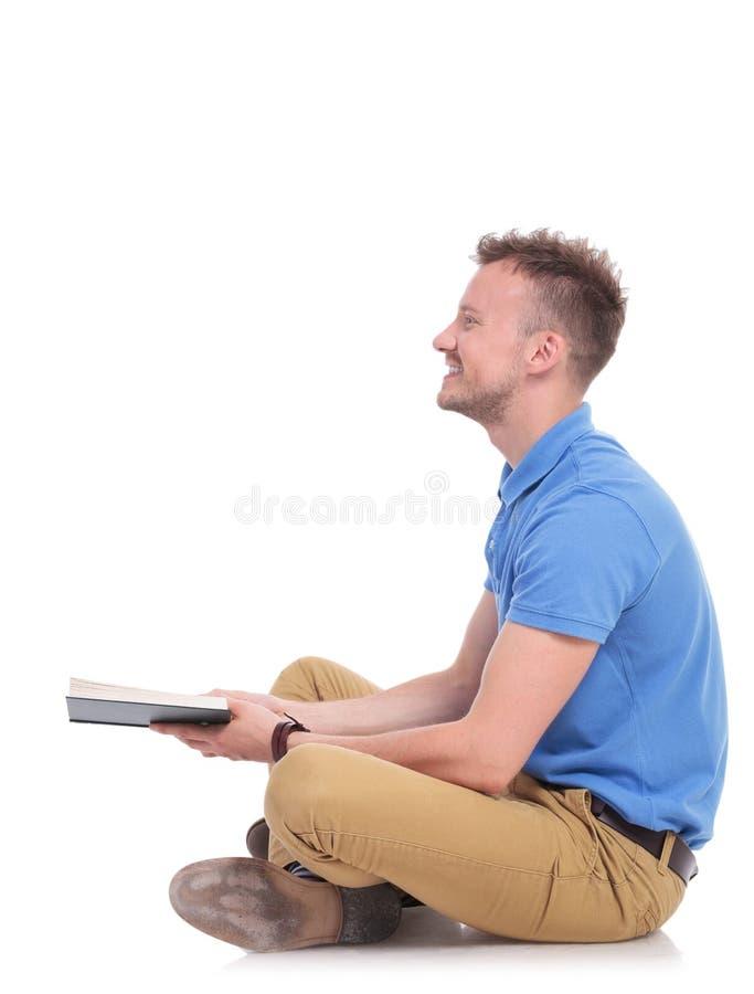 Strona posadzony młody człowiek trzyma książkę zdjęcie royalty free