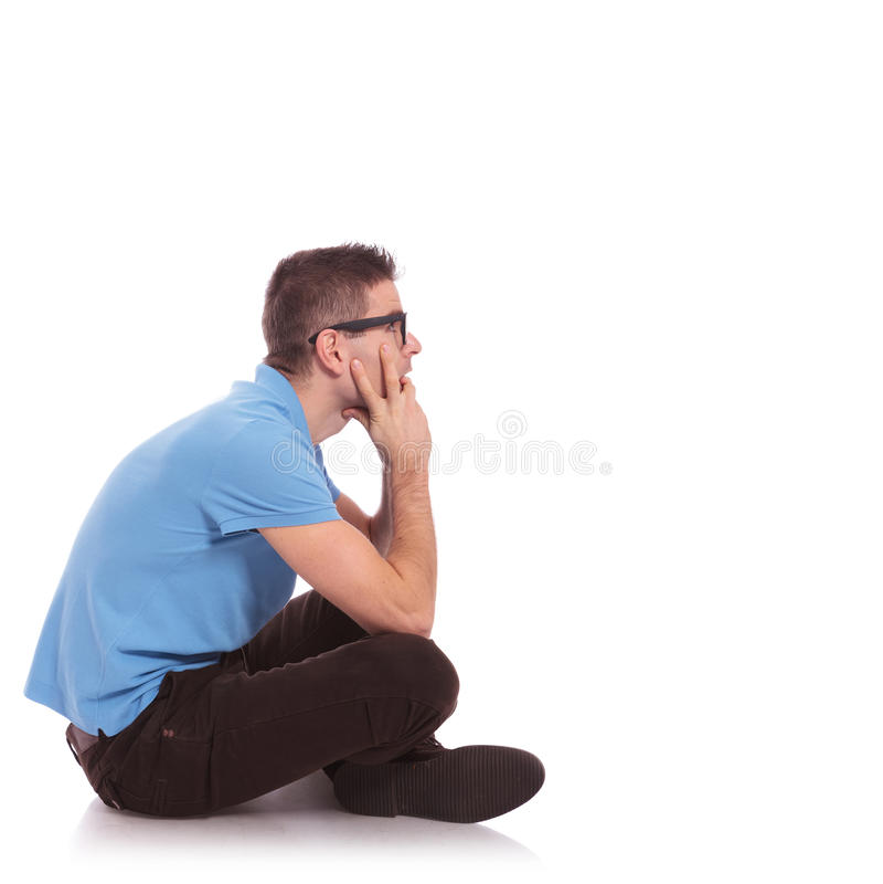 Strona przypadkowy mężczyzna obsiadanie z nogami krzyżować obrazy stock