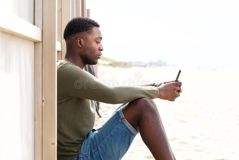 Strona przystojny młody murzyn siedzi outdoors z telefonem komórkowym zdjęcia royalty free