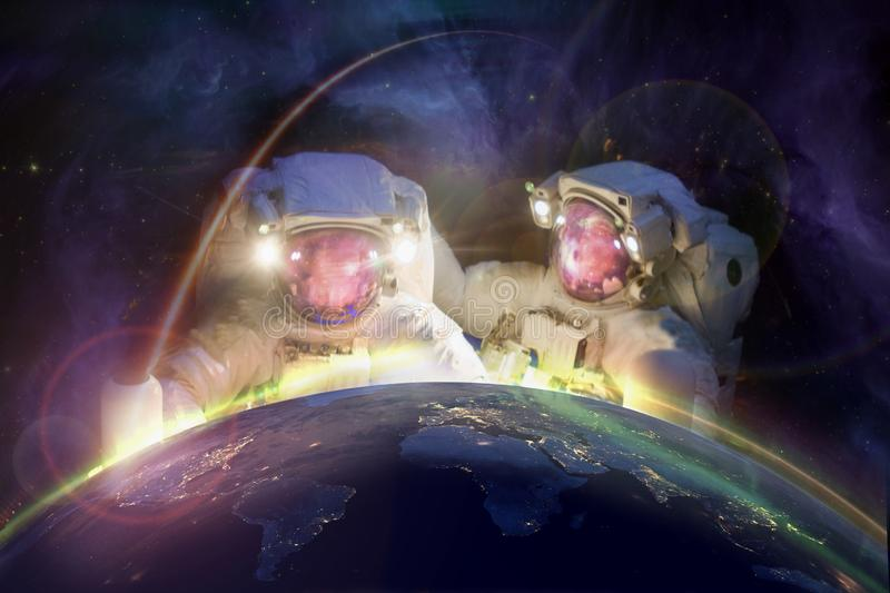 Stronauts look at planet earth from space. Two huge astronauts look at planet earth from space against the background of the galaxy. Elements of this image stock image