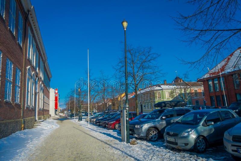 STRONDHEIM, NORUEGA - 4 DE ABRIL DE 2018: La vista al aire libre de coches parqueó en fila en la calle en escandinavo tradicional imagen de archivo