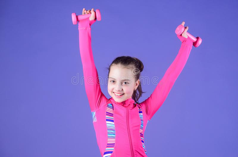 Strong and adorable. Small baby developing strength with dumbells. Fit kid exercising her strength. Cute girl have. Physical training of muscular strength royalty free stock photo