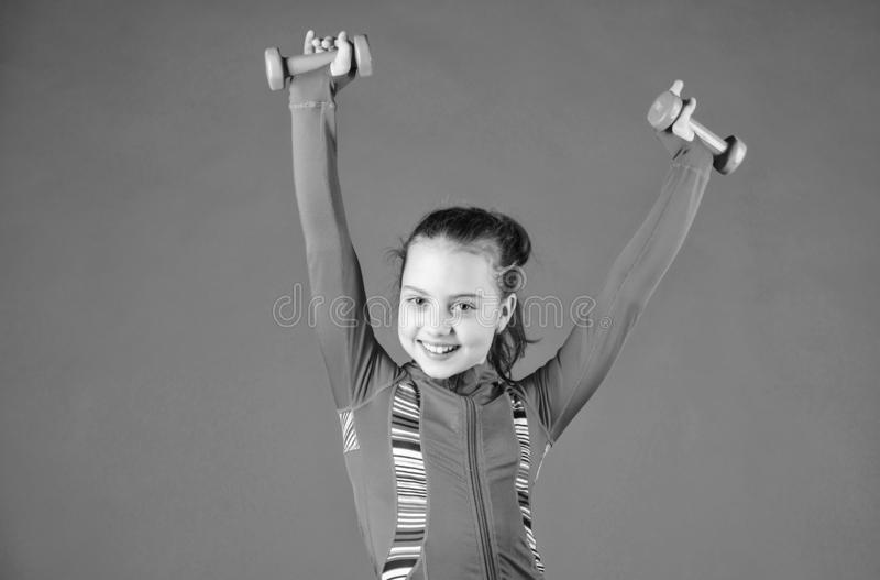 Strong and adorable. Small baby developing strength with dumbells. Fit kid exercising her strength. Cute girl have. Physical training of muscular strength royalty free stock photography