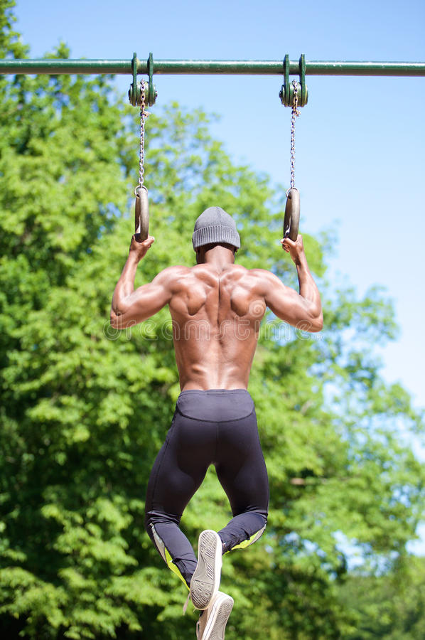 Strong african american man pulling up on gymnast rings royalty free stock photo