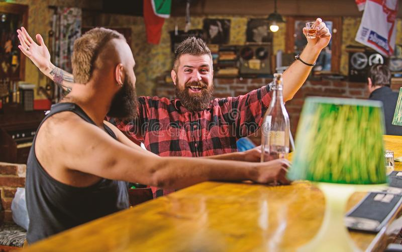 Strong alcohol drinks. Alcohol addiction. Friends relaxing in pub. Men drunk relaxing at pub having fun. Hipster brutal stock image