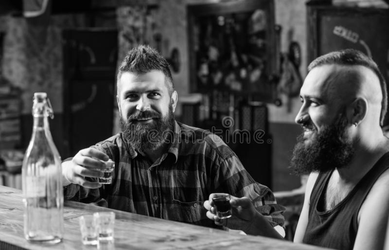 Strong alcohol drinks. Friends relaxing in pub. Men drinking alcohol together. Alcohol addiction. Hipster brutal man stock image