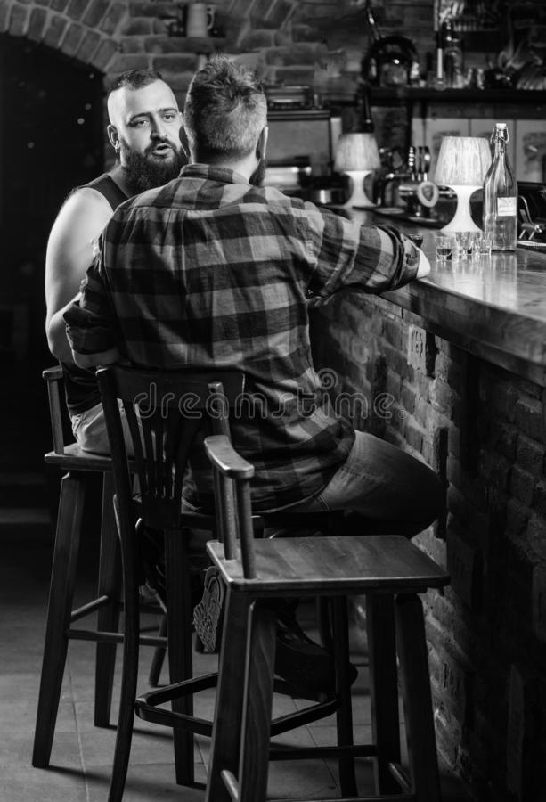 Strong alcohol drinks. Opening hours till last visitors. Friday relaxation in bar. Men relaxing at bar. Friends relaxing. In bar or pub. Hipster bearded men stock image