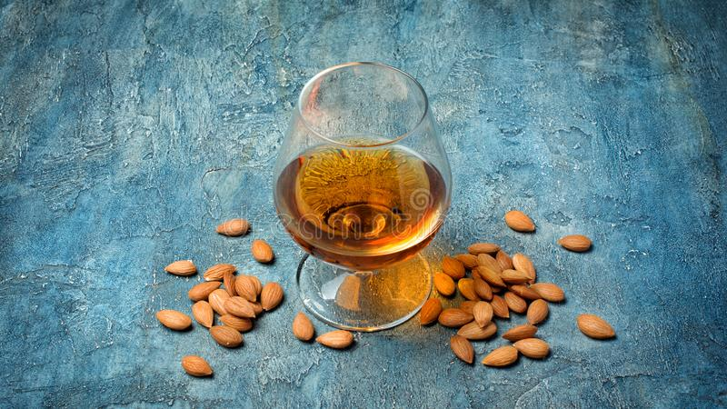 Strong alcoholic drink amaretto liqueur for tasting. Strong alcoholic beverage amaretto liqueur in sniffer glass for tasting on blue concrete background royalty free stock photography