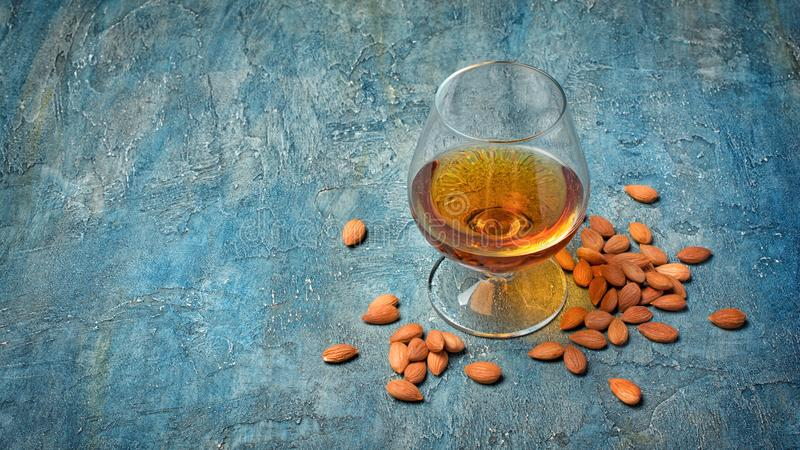 Strong alcoholic drink amaretto liqueur for tasting. Strong alcoholic beverage amaretto liqueur in sniffer glass for tasting on blue concrete background with stock photos