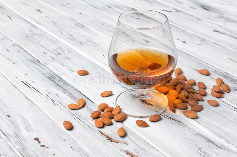 Strong alcoholic drink amaretto liqueur for tasting. Strong alcoholic beverage amaretto liqueur in sniffer glass for tasting on white wooden background with copy stock images