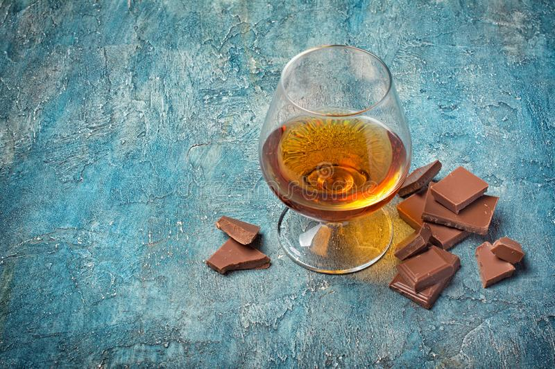 Strong alcoholic drink cognac with chocolate bar. Strong alcoholic beverage cognac in sniffer glass with chocolate bar for tasting on blue concrete background stock images