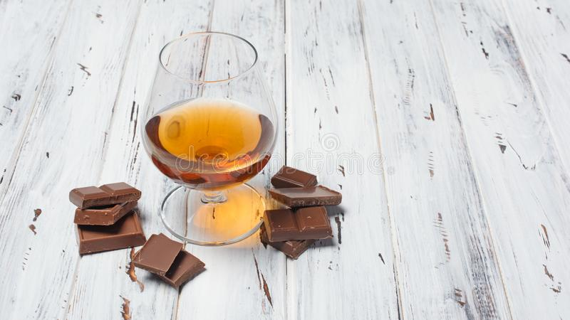 Strong alcoholic drink cognac with chocolate bar. Strong alcoholic beverage cognac in sniffer glass with chocolate bar for tasting on white wooden background royalty free stock photography