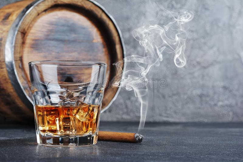 Strong alcoholic drink scotch whisky with ice cubes in old fashion glass with smoking cigar and vintage wooden barrel in cellar. On gray concrete background royalty free stock images