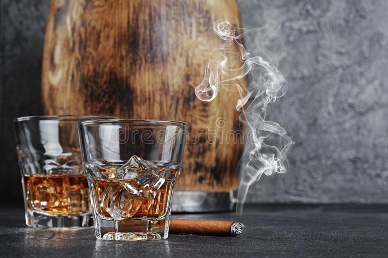 Strong alcoholic drink scotch whisky with ice cubes in old fashion glasses with smoking cigar and vintage wooden barrel in cellar. On gray concrete background royalty free stock image