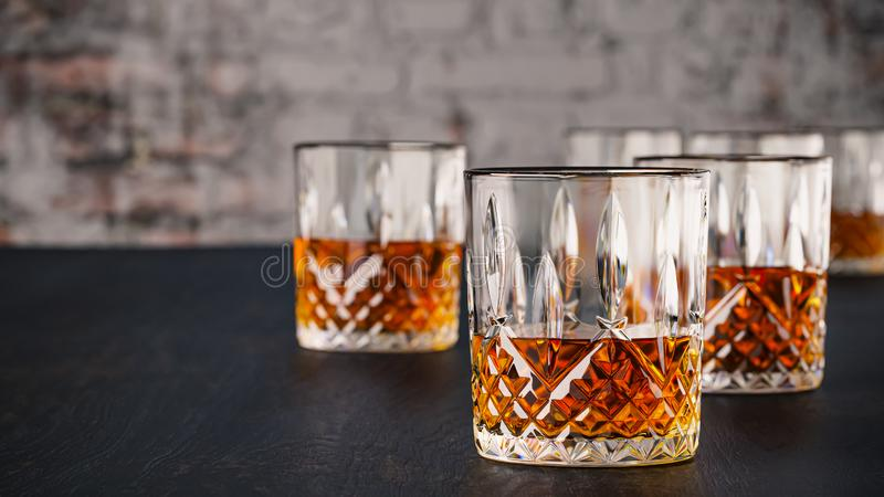 Strong alcoholic drinks, glasses and glasses, in the presence of whiskey, brandy. on a dark background of an old wooden table. Shabby brick wall with selective stock photos
