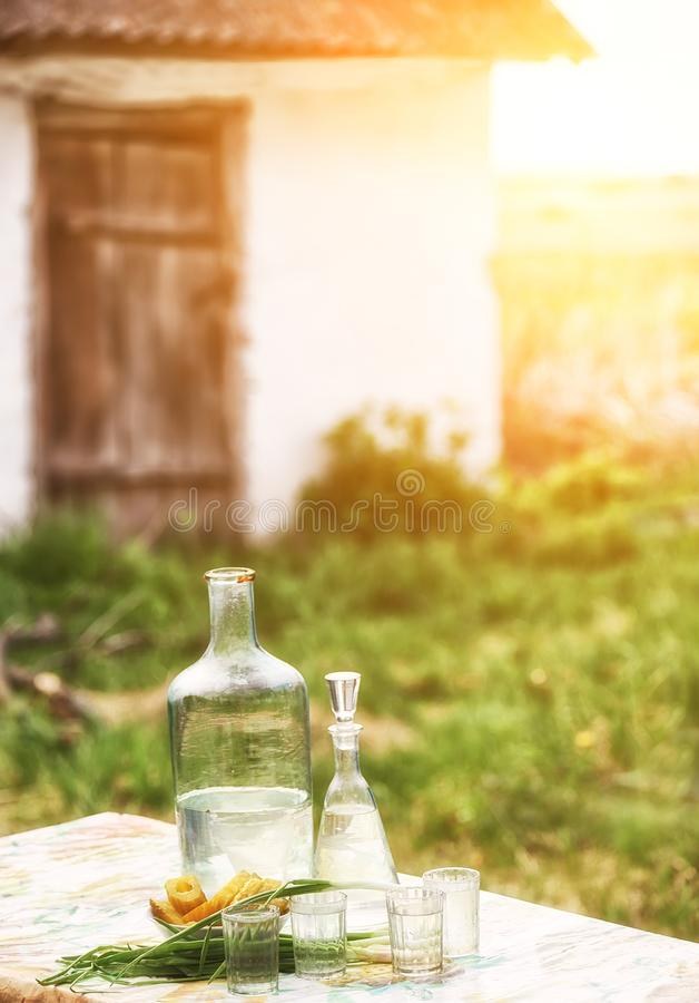 Strong alcoholic homemade drink moonshine in glass vintage containers and pickled cucumbers. Traditional rural still life of Ukrai. Ne stock image