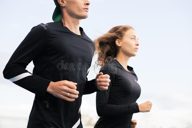 Strong and ambitious couple running outdoors royalty free stock image