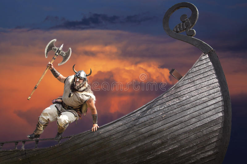 Strong angry bearded Viking with axe jumping stock photos