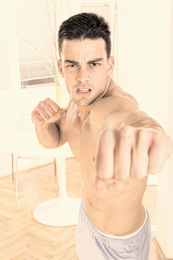 Strong angry handsome man fighter punching towards camera stock image