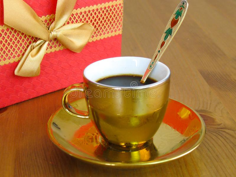 Strong aromatic coffee in a gilded cup with a golden spoon. On the background of a wooden table stock photo