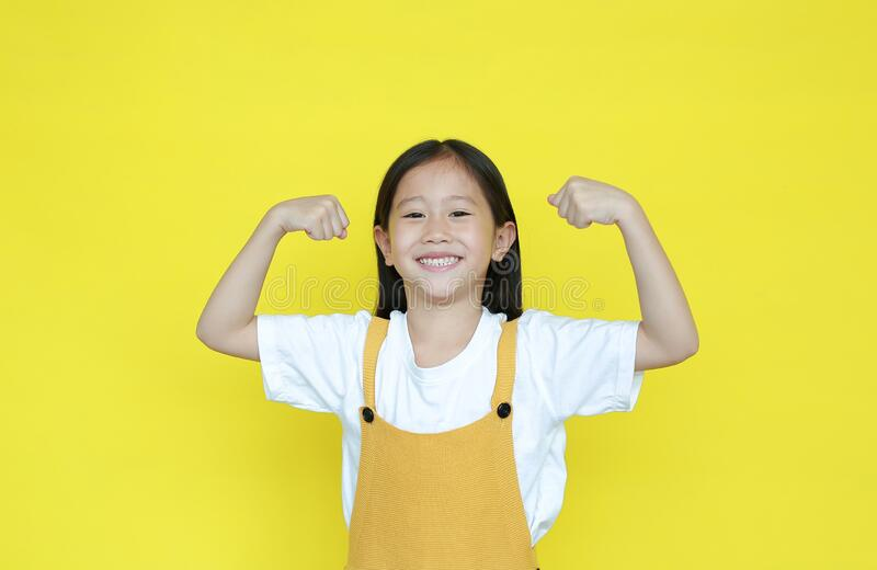 Strong asian little girl raising hands up and smiling. Portrait of happy child in dungarees isolated on yellow background. Good royalty free stock photography
