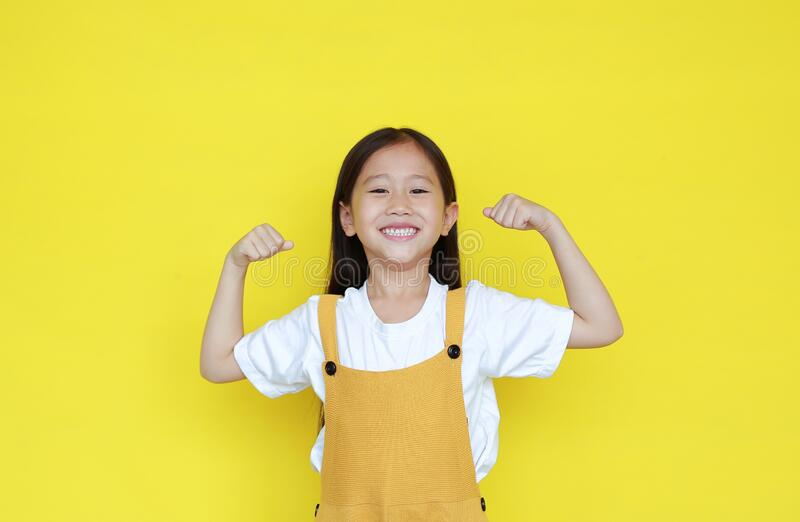 Strong asian little kid girl raising hands up and smiling. Portrait of happy child in dungarees isolated on yellow background stock photos
