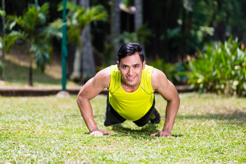 Strong Asian man doing sport push-up in park. Looking at camera stock images