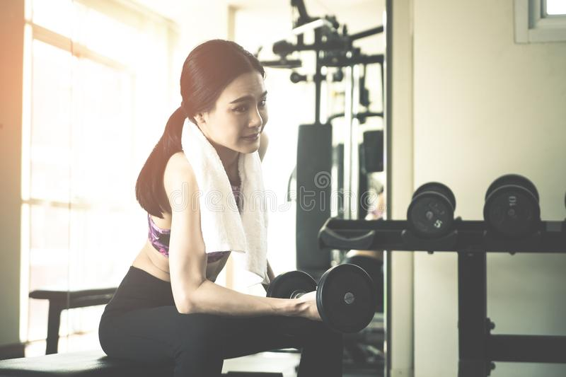 Strong Asian woman is lifting dumbbell in fitness royalty free stock images